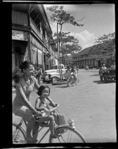 Scène de rue à Papeete, femme et enfant à vélo (1952)