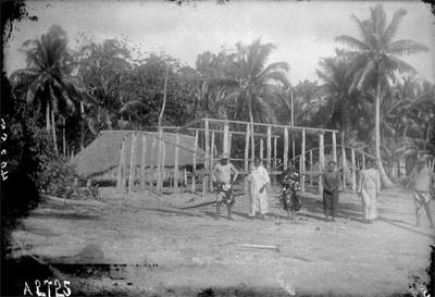 Polynésiens devant l'ossature en bois d'une habitation (1900)