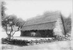 Marquisiens devant une maison traditionnelle sur plateforme en pierre (1909)